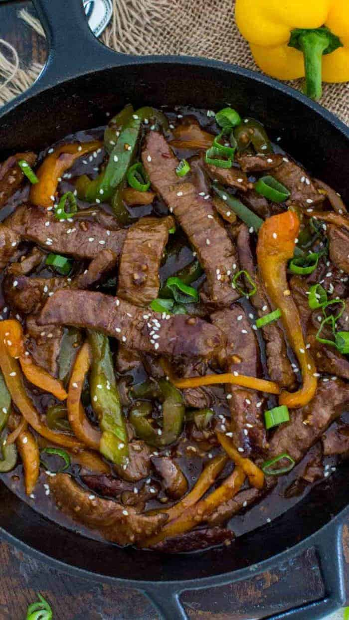 Cast iron skillet of One Pan Pepper Steak with peppers garnished with sesame seeds and green onions, with a yellow pepper in the background