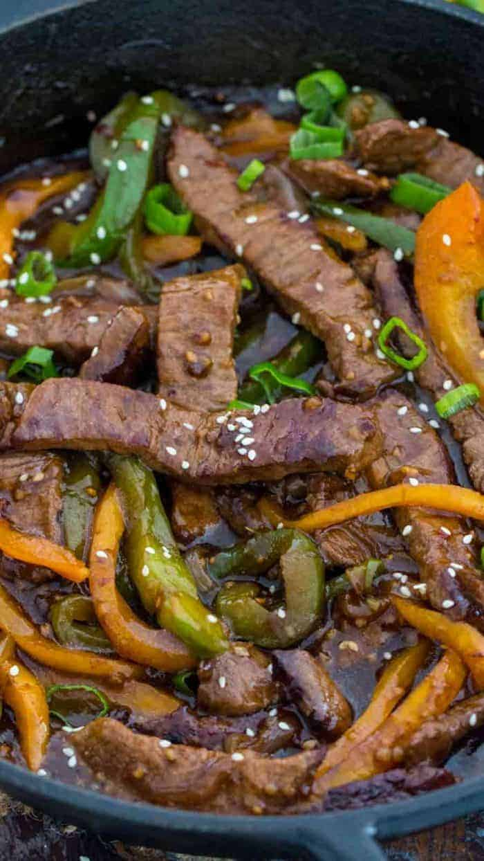close of up cast iron skillet of One Pan Pepper Steak with peppers garnished with sesame seeds and green onions