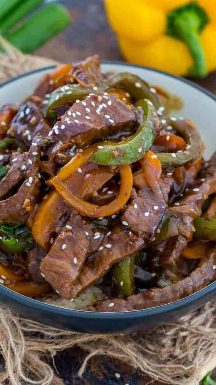 Bowl of One Pan Pepper Steak with peppers garnished with sesame seeds and green onions, with a yellow pepper in the background