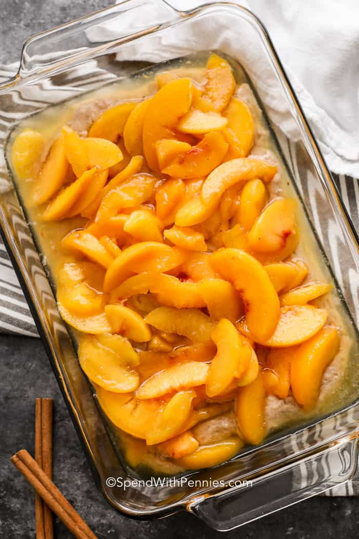 Assembled peach cobbler in a baking dish like peaches and batter.