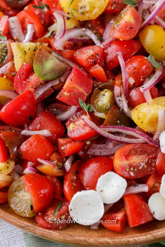 Tomato salad with herbs, seasonings and oil & vinegar on a wood plate