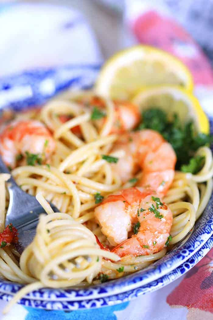 a forkful of Shrimp Scampi with pasta from a fancy blue bowl garnished with lemon slices and parsley