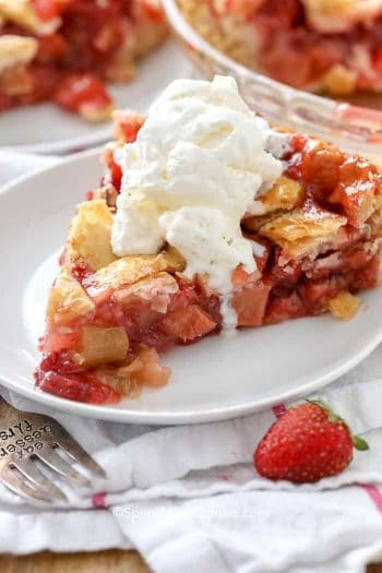 Strawberry Rhubarb Pie on a white plate with vanilla ice cream on top