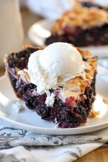 Slice of Blueberry Pie on a white plate with ice cream on top