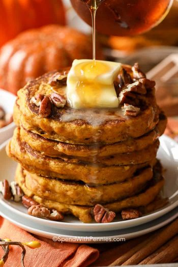 Pouring syrup over a stack of Pumpkin Pancakes