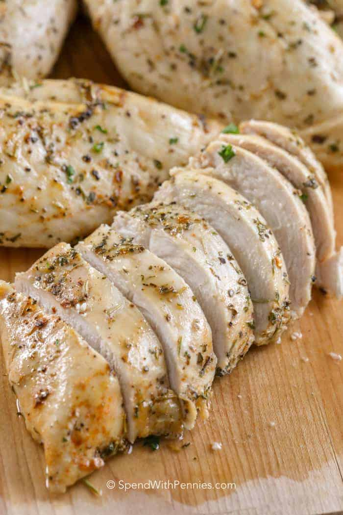 Plump sliced chicken breasts ready to be served on a wooden cutting board.