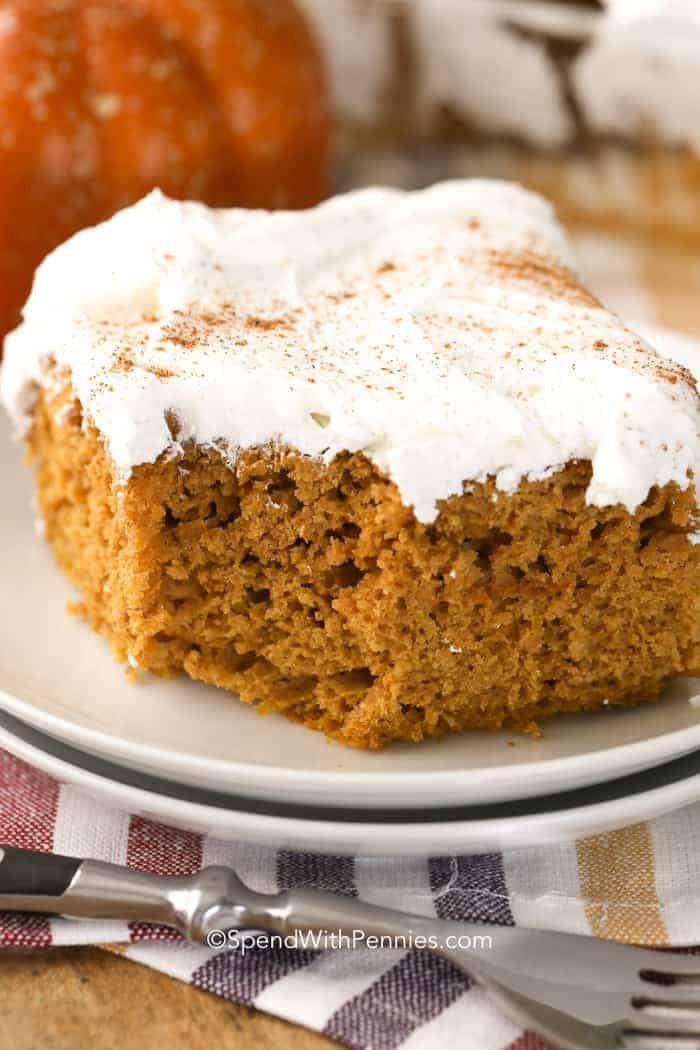 A slice of Pumpkin Dump Cake topped with whipped topping and a sprinkle of cinnamon, on a white plate