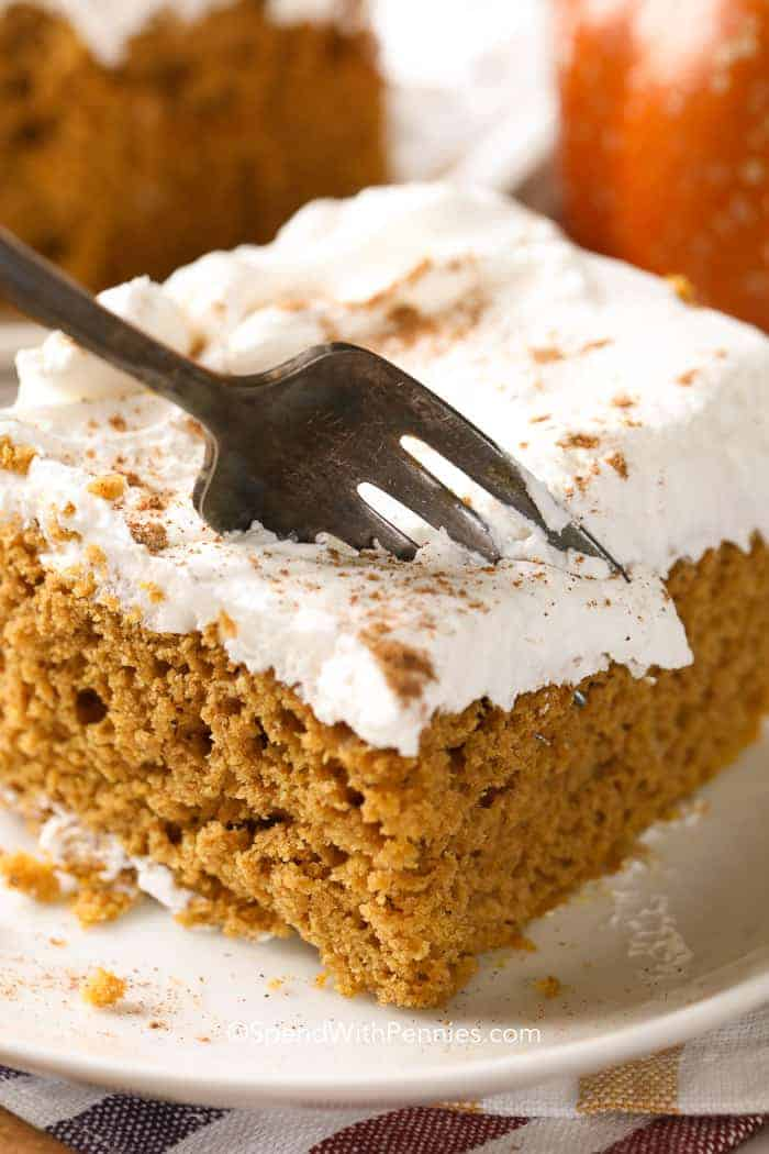 A close up picture of Pumpkin Dump Cake, on a white plate with a fork taking out a bite sized piece