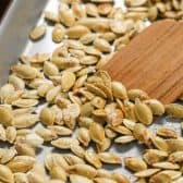 Using a wooden spatula to lift out Roasted Pumpkin Seeds from a baking sheet