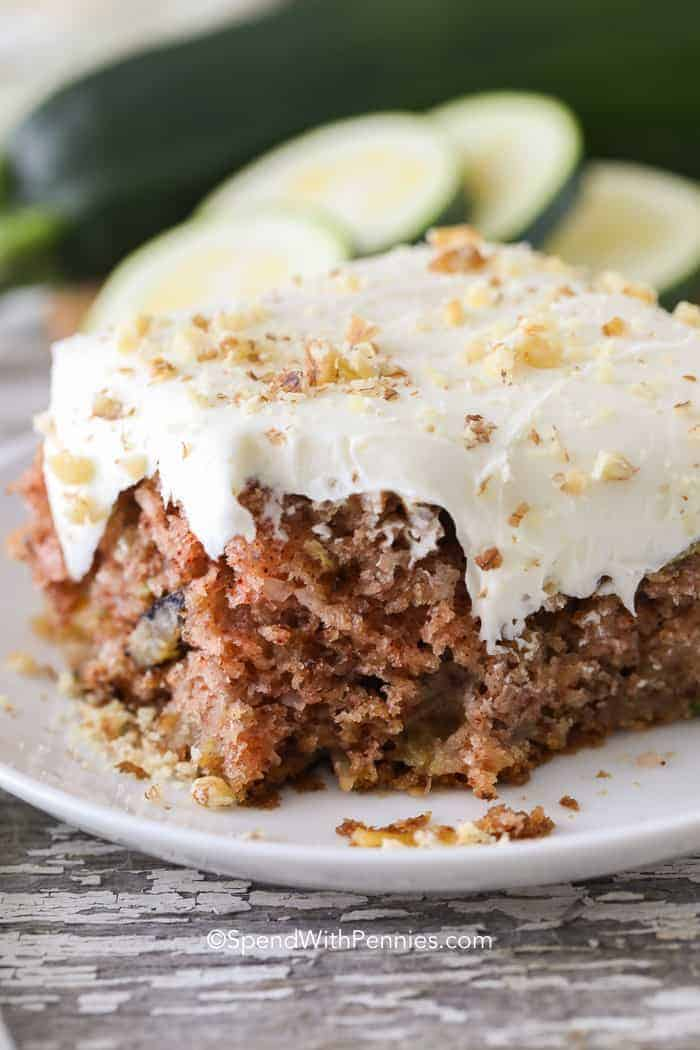 Zucchini Cake on a white plate with bite taken out of it