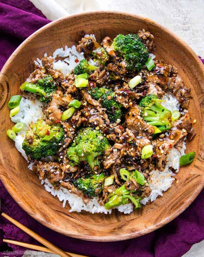 Beef and broccoli in wooden bowl on a bed of rice