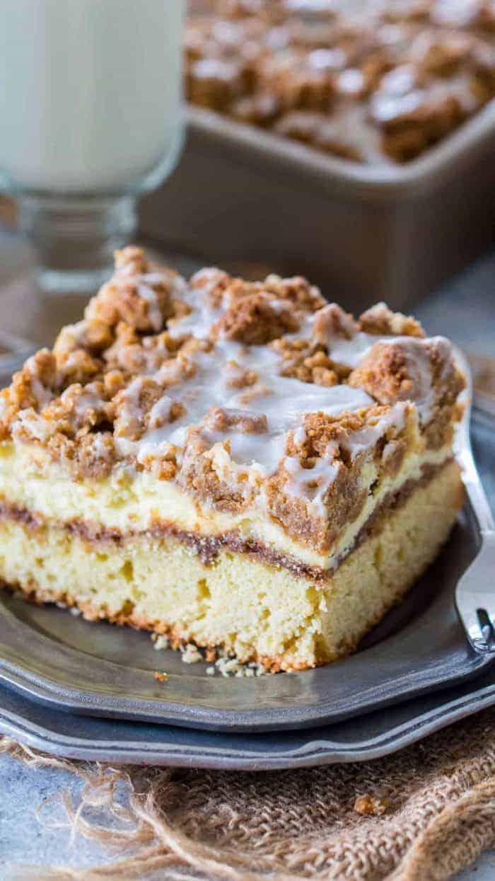 Coffee Cake topped with cinnamon filling, vanilla cheesecake and a sweet streusel topping on a grey plate with a fork, and the cake pan in the background
