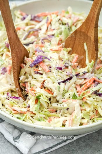 Bowl of Coleslaw in a bowl with two wooden serving spoons