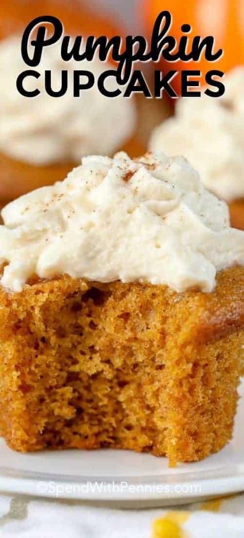 Pumpkin Cupcake topped with whipped cream and a bite taken out.