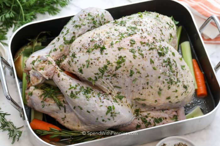 A raw turkey in a roasting pan with veggies. Garnished with parsley, thyme, and rosemary.