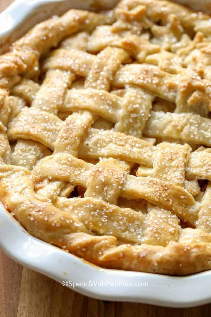 Apple pie in a pie plate with a golden flaky pie crust filled with cinnamon apples.