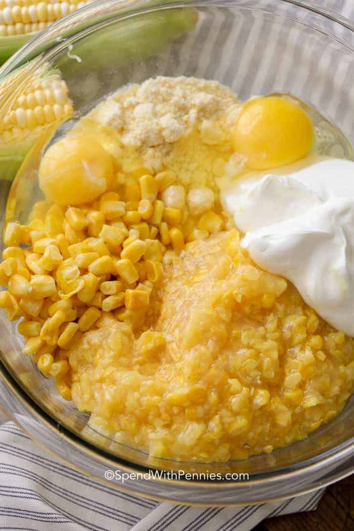 A clear bowl full of corn casserole ingredients like cornbread mix, creamed corn, and regular corn.