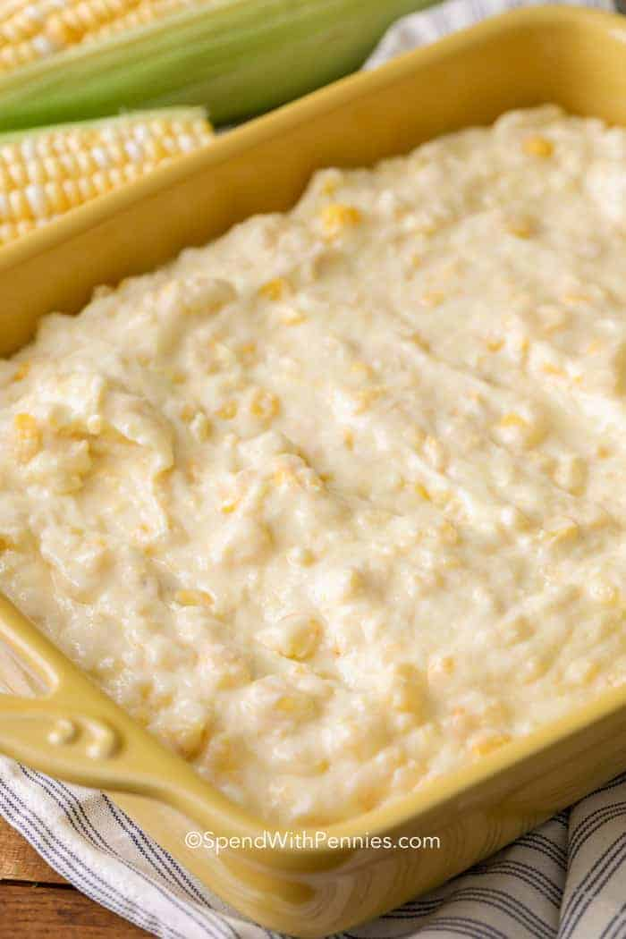 Corn casserole mix in a yellow casserole dish surrounded by fresh corn.