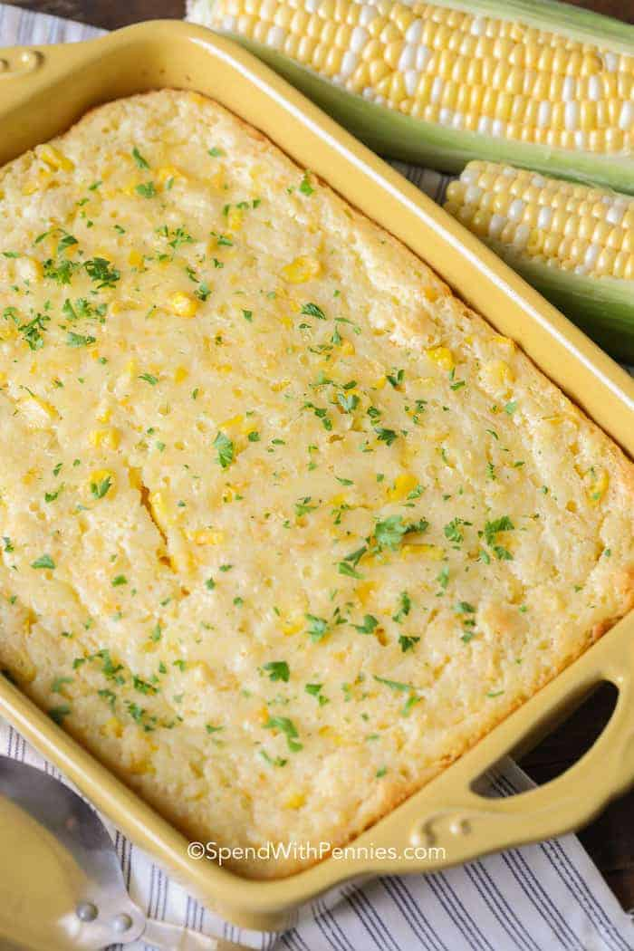 Buttery and golden corn casserole fresh from the oven topped with fresh parsley.
