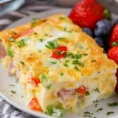 Piece of Denver Egg Casserole on a plate with strawberries and blueberries