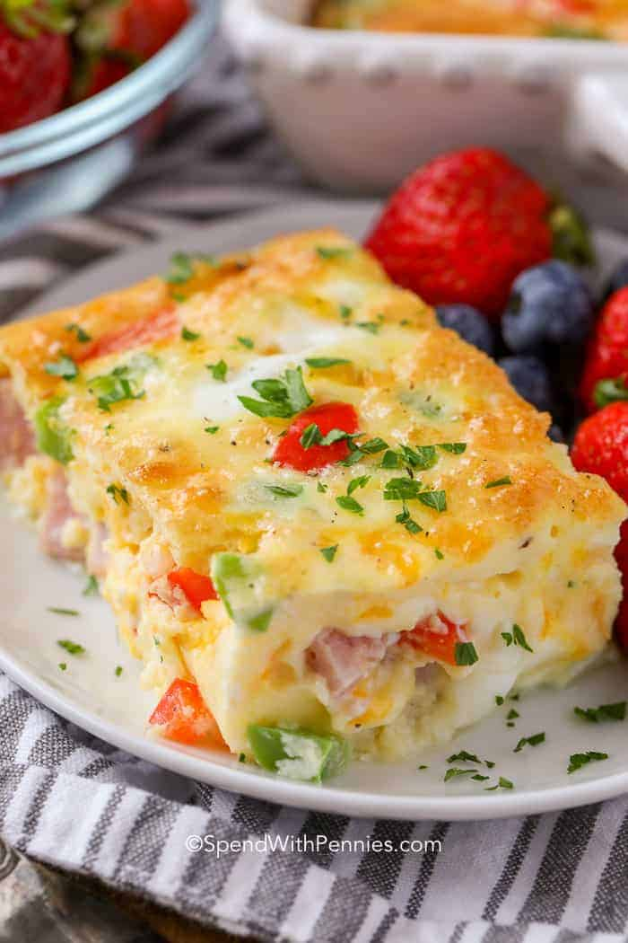 A slice of Denver Egg Casserole on a plate with berries