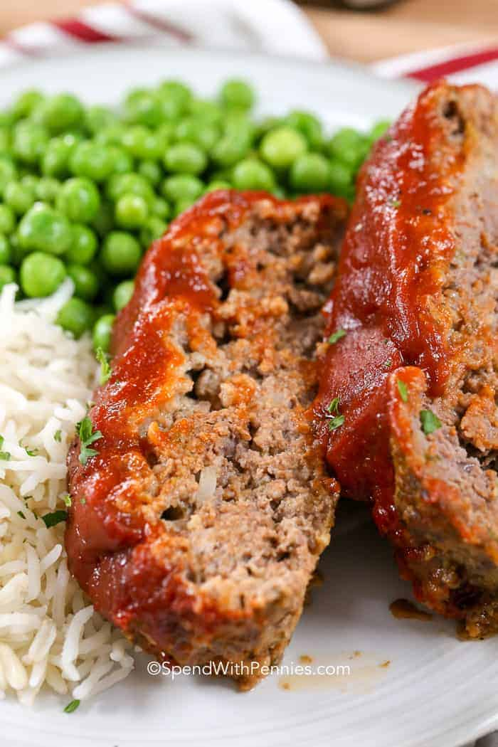 Two slices of glazed meatloaf on a plate with rice and green peas