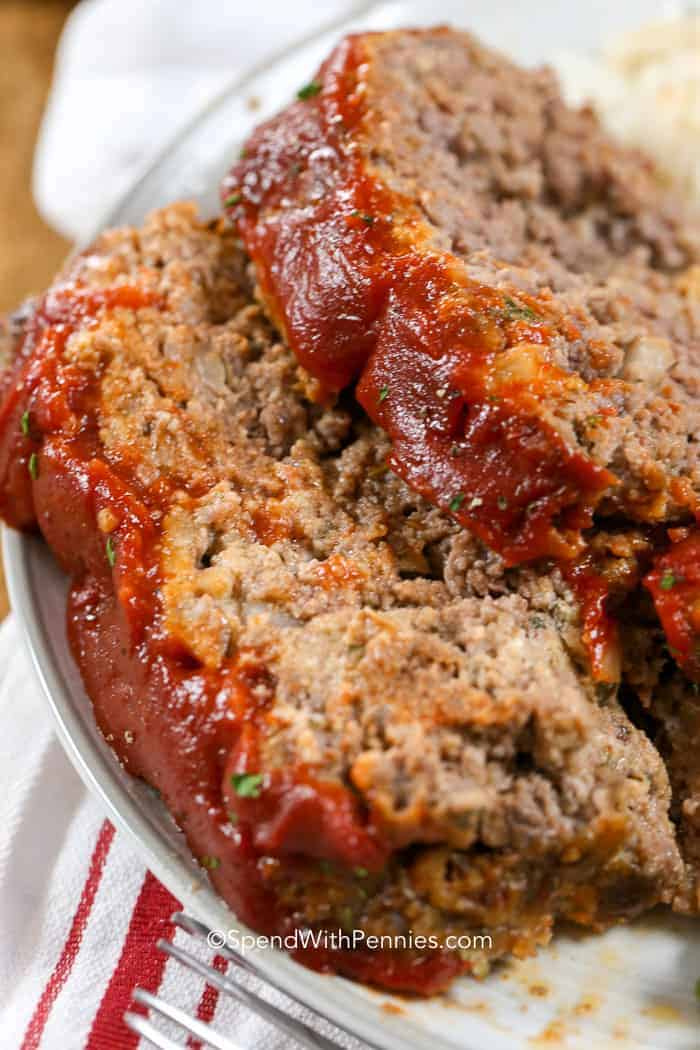 Juicy meatloaf recipe topped with chili sauce and ketchup.