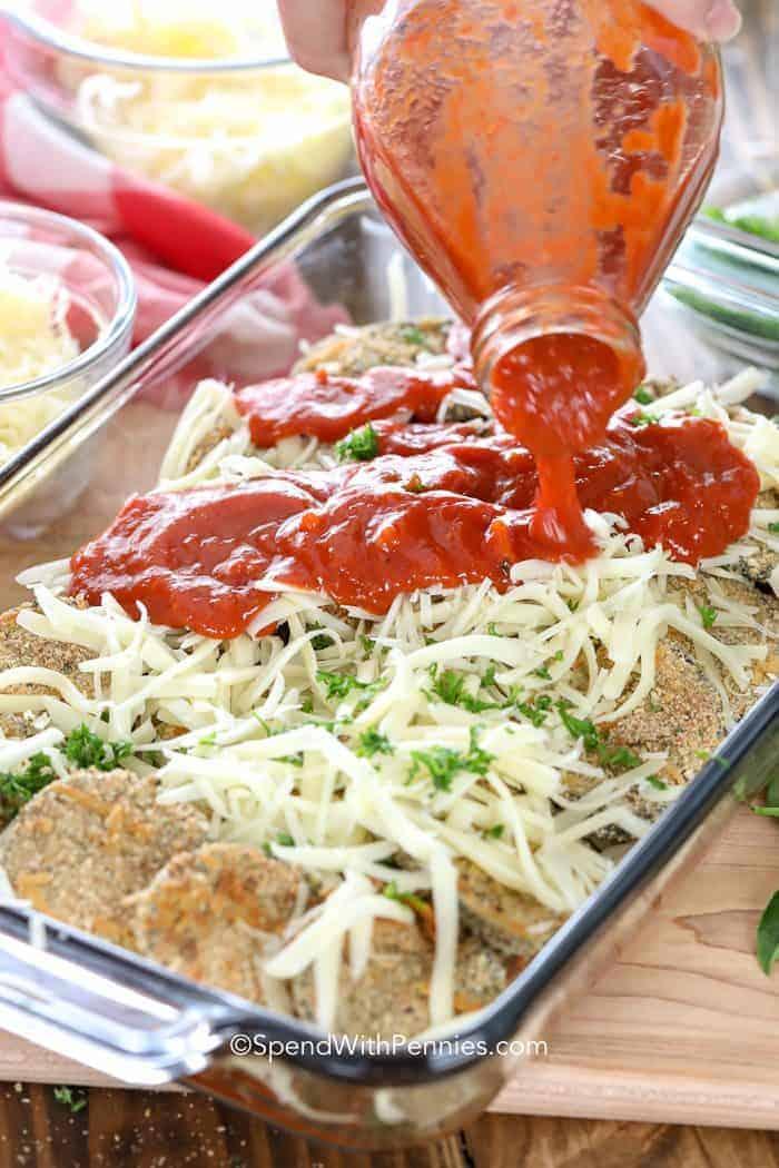 Pouring marinara sauce on baking dish of uncooked Eggplant Parmesan