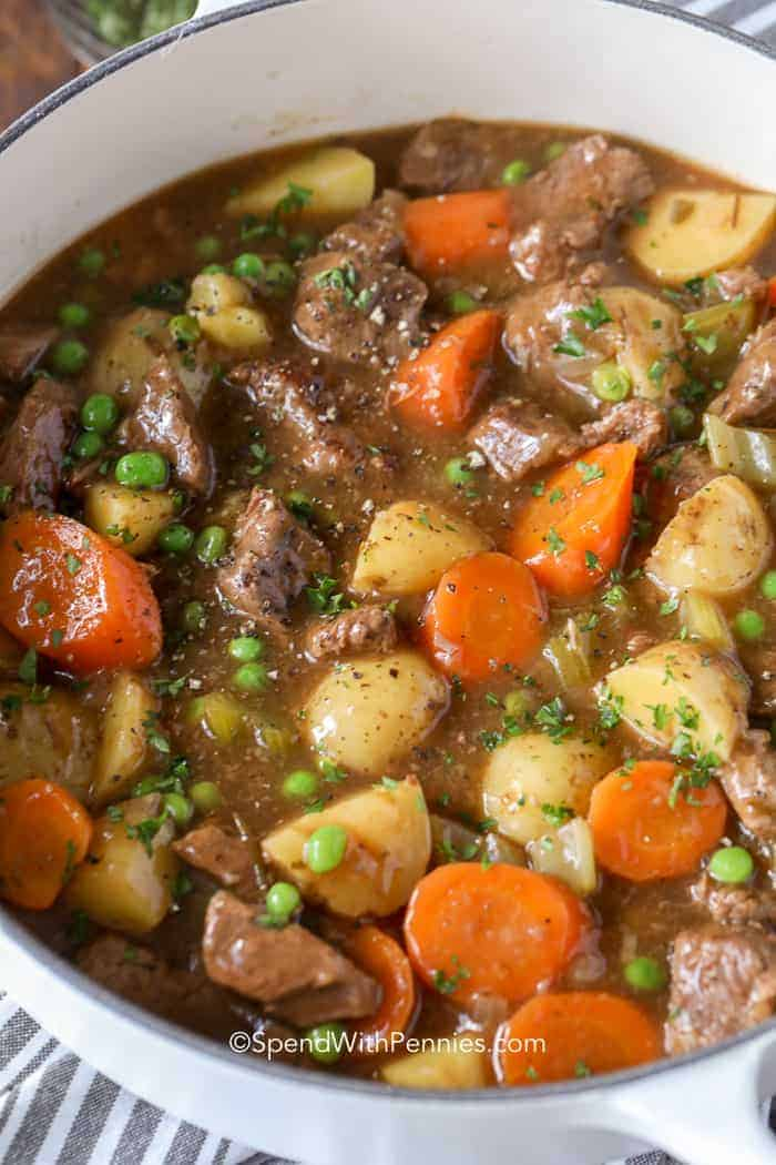 A close up of flavorful beef stew full of carrots, potatoes, peas, and beef.
