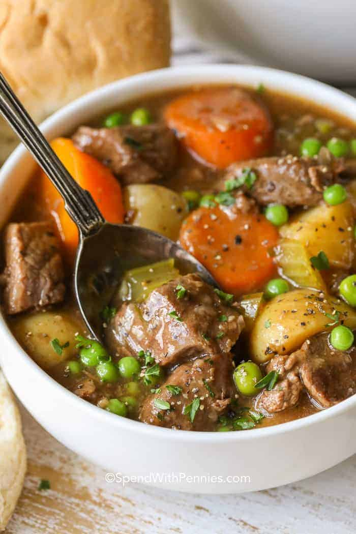 A white bowl of tender beef stew being scooped with a silver spoon.