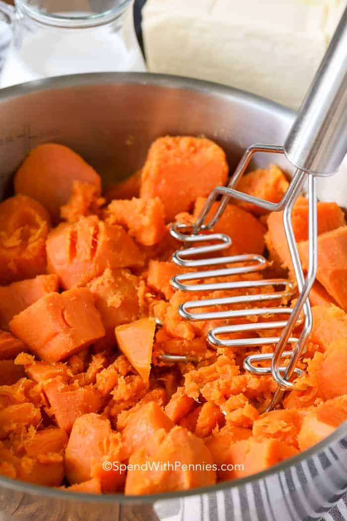 Sweet Potatoes being mashed in a large pot for mashed sweet potatoes