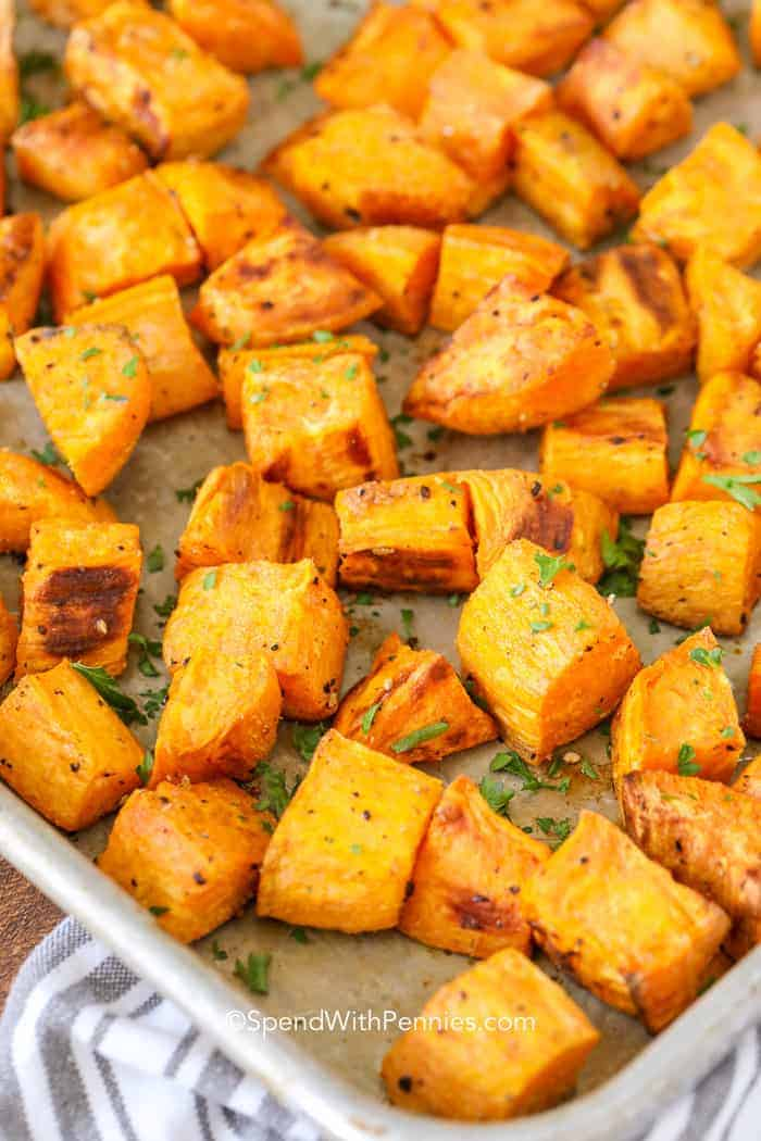 A baking sheet with cooked and golden roasted sweet potatoes scattered on it