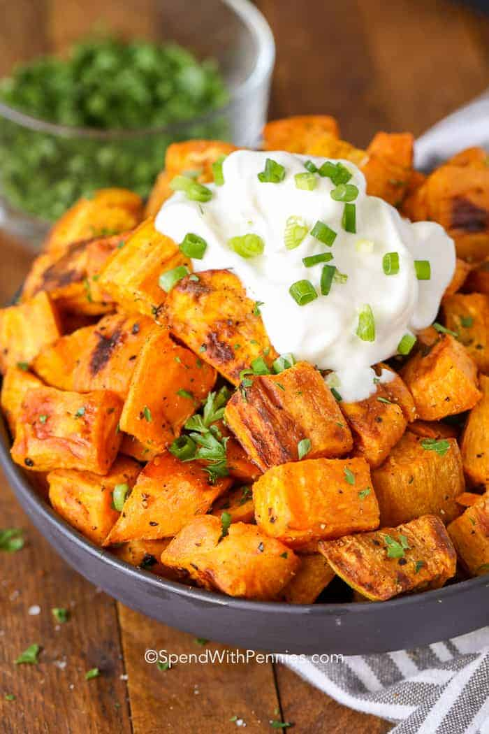 Roasted Sweet Potatoes in a bowl with sour cream and chives on top
