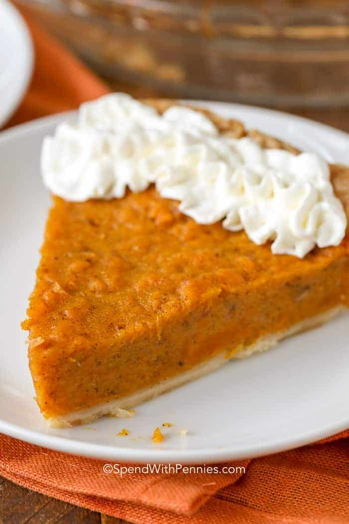 A slice of sweet potato pie served on a white plate and garnished with whipped cream