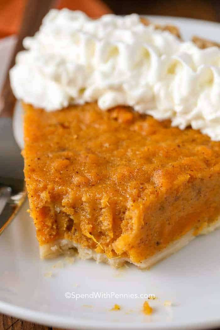 A slice of sweet potato pie garnished with whipped cream