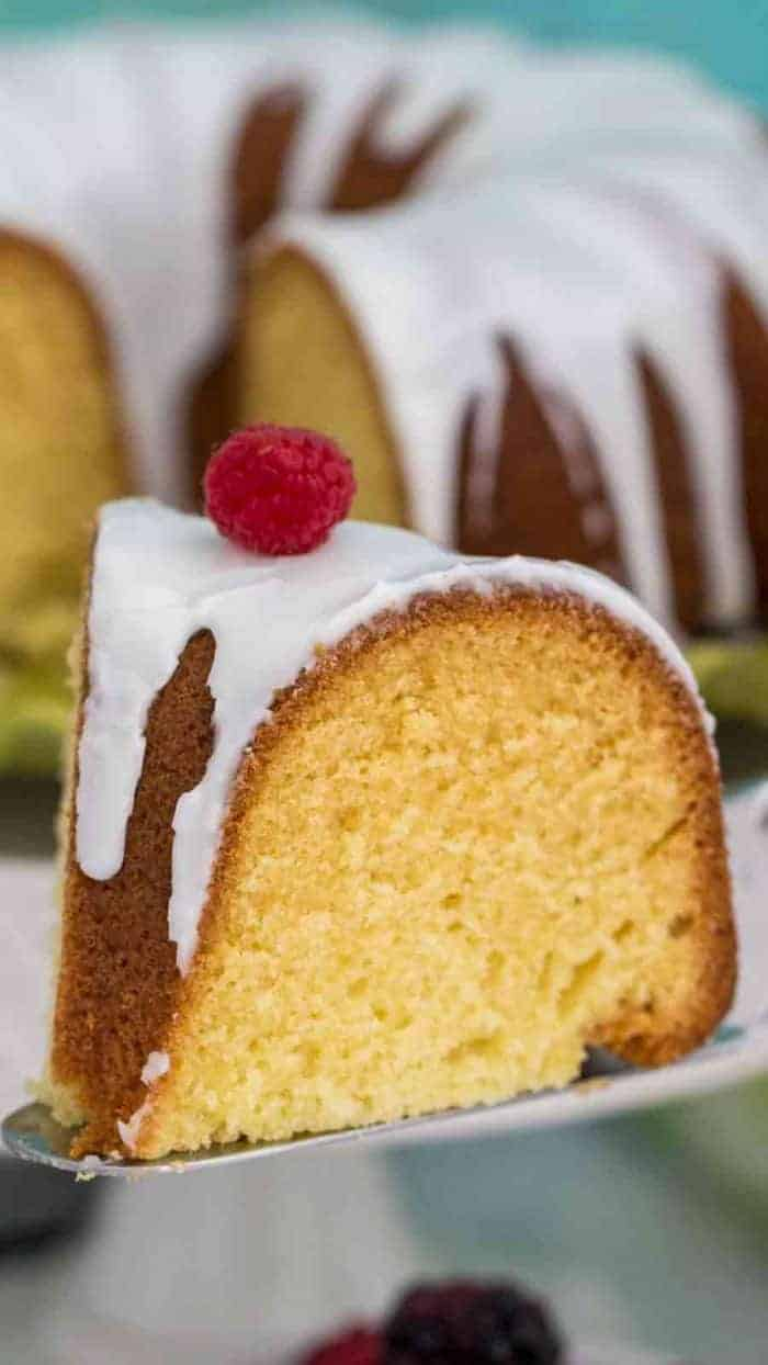 a gorgeous slice of Vanilla Bundt Cake with vanilla glaze topped with a raspberry and the cake in the background