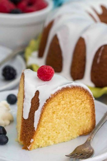 Slice of Vanilla Bundt Cake on white plate with berries and a fork