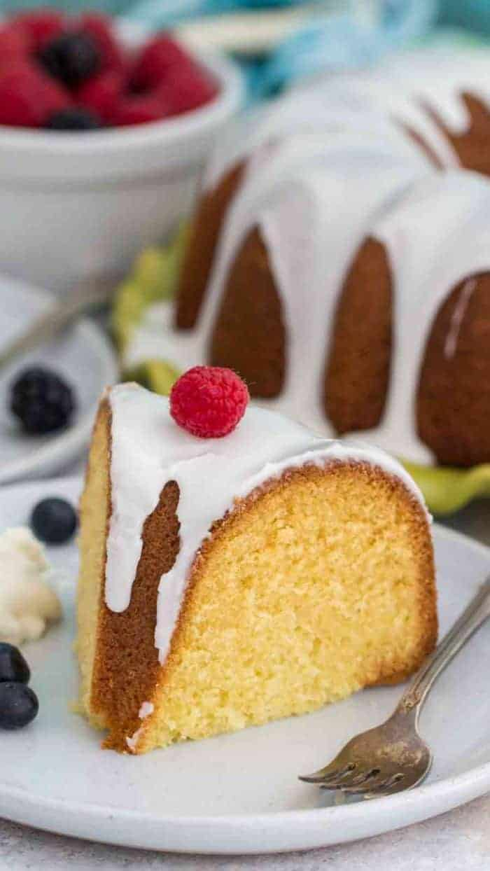 Vanilla Bundt Cake topped with vanilla glaze and a raspberry on a white plate, with a fork, with the bundt cake and a bowl of berries in the background