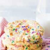 White Chocolate Funfetti Sugar Cookies, a stack of 3, with a glass of milk behind, sitting on a pink napkin