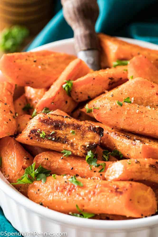 Bowl of freshly roasted carrots garnished with parsley - the perfect Thanksgiving side