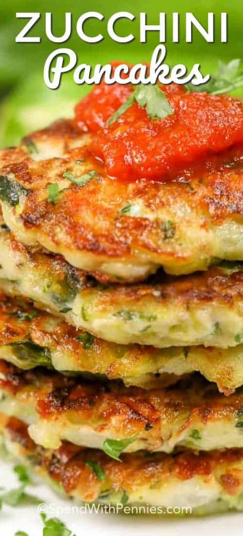 Zucchini pancakes piled up on each other and topped with tomato sauce