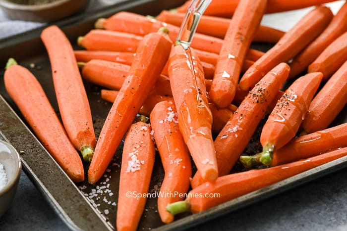 Raw carrots on a sheet pan with olive oil being poured on