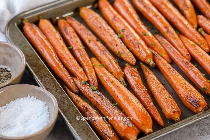 Freshly roasted carrots on a baking pan garnished with salt and pepper
