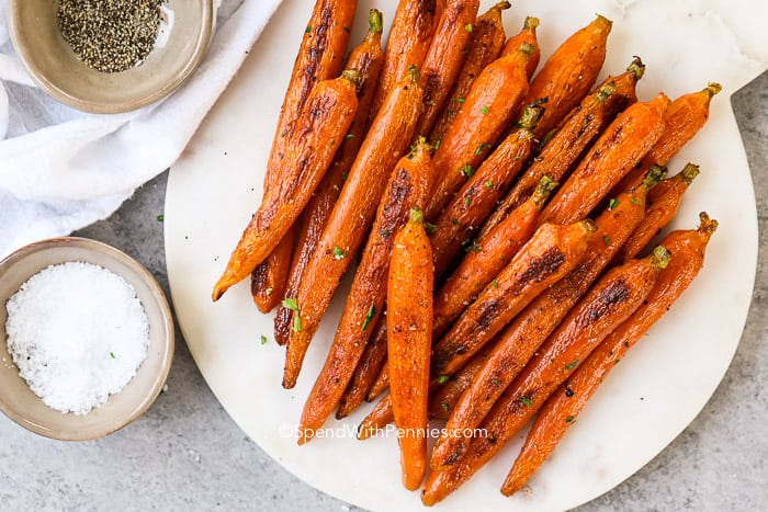 Roasted carrots on a marble board with salt and pepper