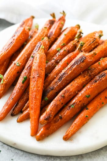 Oven roasted carrots on a marble board garnish with parsley