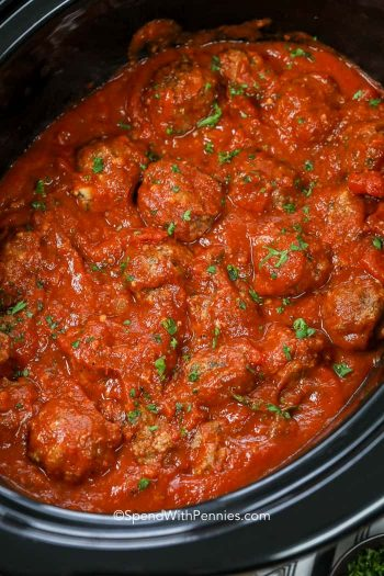 Meatballs cooking in black slow cooker
