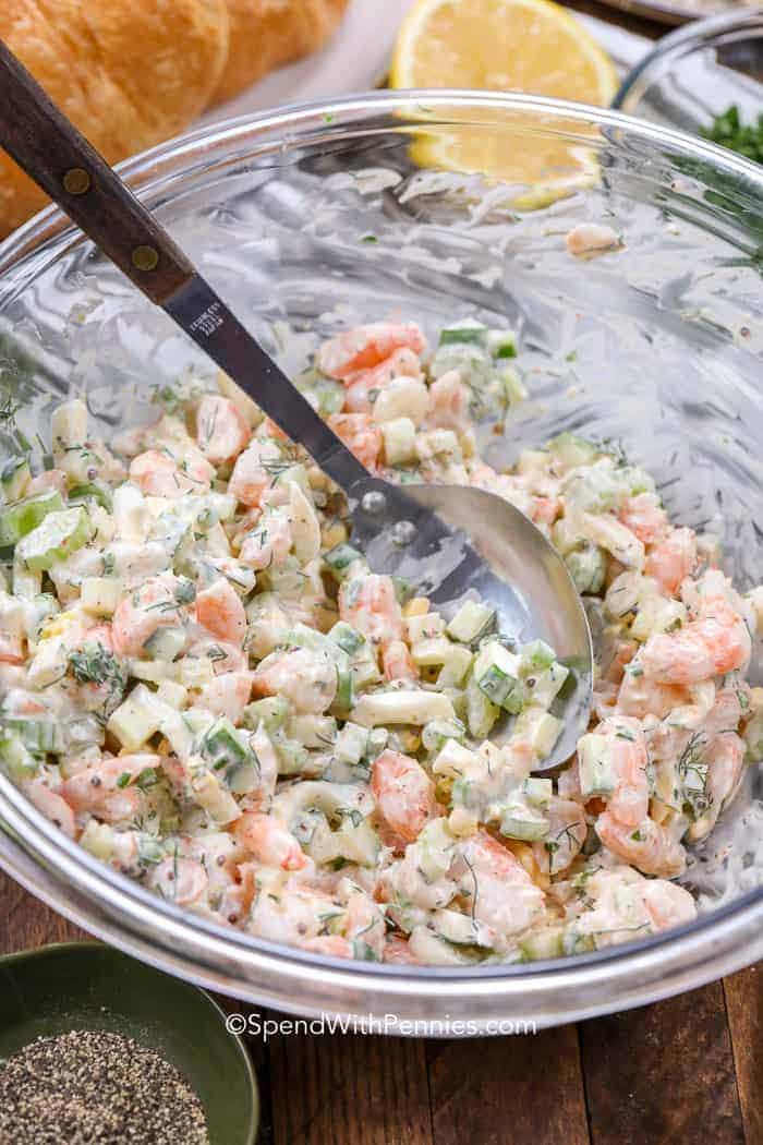 Stirring Shrimp Salad in a clear glass bowl with a silver spoon