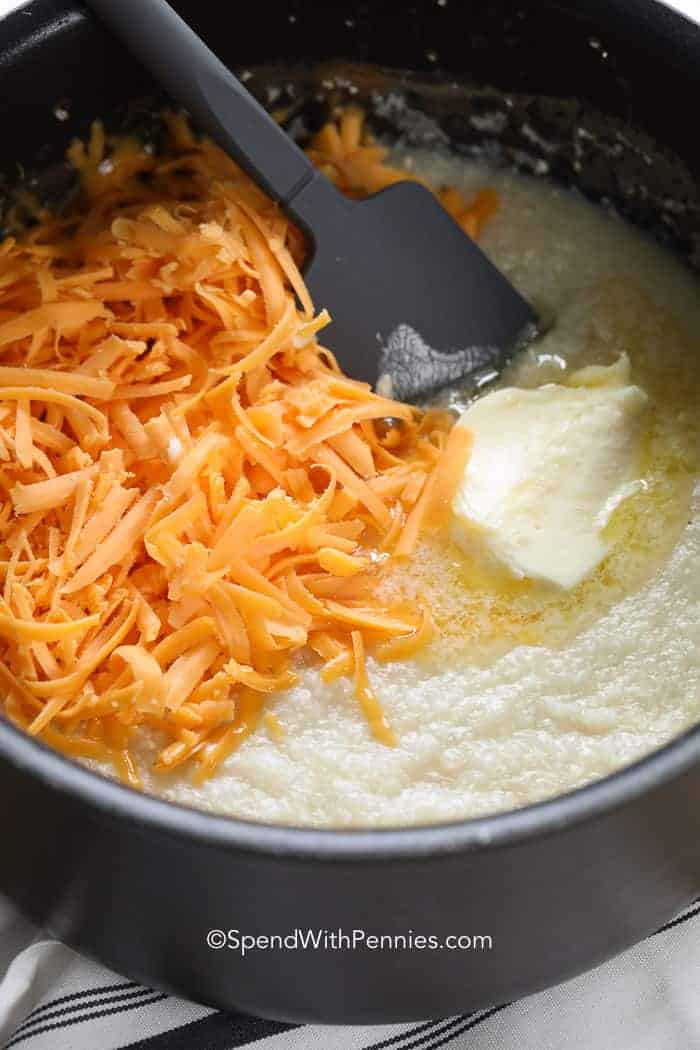 Shredded cheese and butter being incorporated into creamy grits in a saucepan