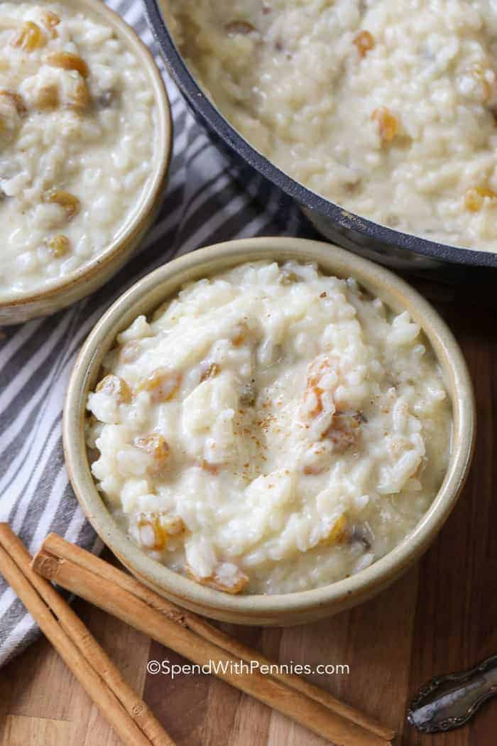 Two individual serving bowls of creamy rice pudding along with a large pot of pudding