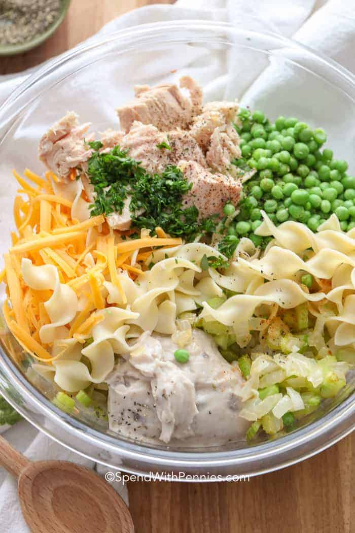Ingredients for easy tuna casserole in a clear bowl including tuna, egg noodles, celery, and peas.